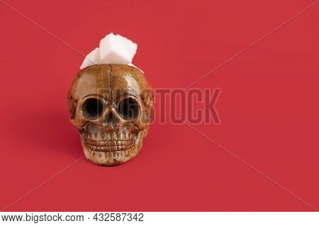 Human Skull Filled With Refined White Sugar Cubes On A Red Background. Selective Focus. Copy Space.