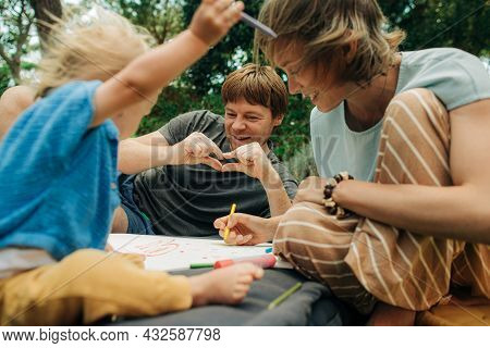 Cheerful Family Having Fun Together In Park. Woman Sitting On Mattress And Painting With Toddler Dau