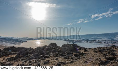 The Frozen Lake Is Surrounded By Snow-covered Hills. The Sun Is Shining In The Blue Sky. Glare On Th