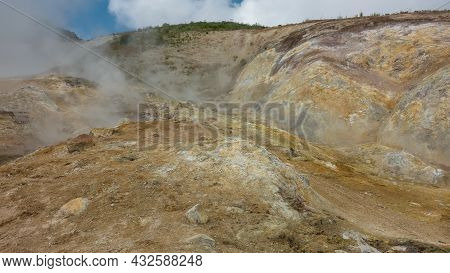 Geothermal Zone On A Mountain Slope. The Soil Is Covered With Yellow-orange Sulfur Deposits. Steam A