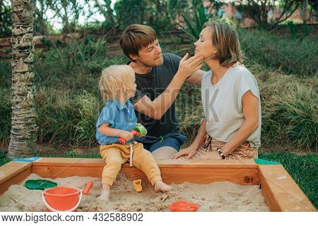 Portrait Of Couple Playing With Child In Sandbox. Man Wiping Face Of His Wife Off Sand While Their D