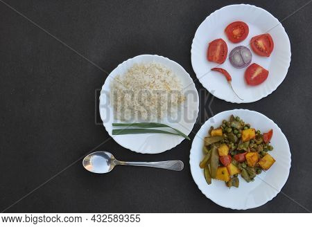 Overhead View Of Rice, Matar Paneer Mix Veg And Salad On White Plate Over Black Background With Nega