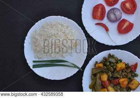 Closeup High Angle View Of Rice, Matar Paneer Mix Veg And Salad On White Plate Over Black Background