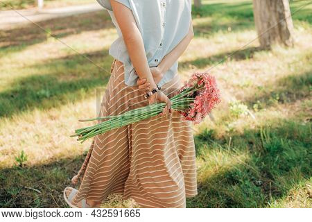 Close-up Of Young Woman Holding Bunch Of Daisies In Hand. Girl Walking Outdoors With Bouquet. Summer