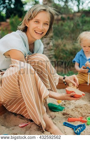 Portrait Of Happy Woman Playing In Sandbox With Her Little Daughter. Mother And Child Spending Time