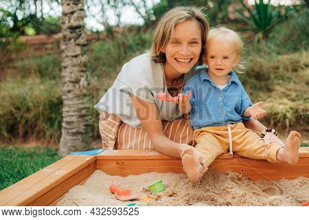 Portrait Of Smiling Mother Playing With Daughter In Sandpit. Happy Mid Adult Woman Embracing Her Lit