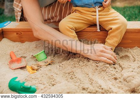 Close-up Of Mother Sitting With Child In Sandpit. Female Hand Touching Leg Of Toddler Sitting In San