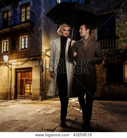 Elegant couple in autumnal coats walking in the rain outdoors at night