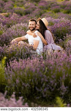 Happy Young Couple Having A Romantic Date At The Lavender Field, Sitting And Hugging, Spending Weeke