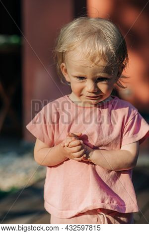 Portrait Of Upset Little Girl Standing Outdoors. Cute Toddler Wearing Pink Tshirt. Childhood Concept