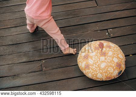 Cute Little Child Standing On Terrace By Cushion. Close-up Of Toddler Wearing Pink Pants Standing On