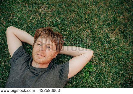 Portrait Of Positive Man Resting On Grass. Mid Adult Guy Having Break Lying On Lawn. Copy Space. Wel