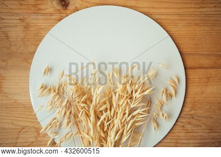 Oat Ears On White Round And Wooden Bagkround. Oat Plant Close Up.