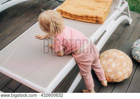 Little Girl Climbing Up Chaise Lounge On Terrace. Cute Toddler Wearing Pink Tshirt And Pants Standin