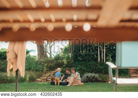 Happy Family Resting Together On Backyard. Mid Adult Man And Woman Sitting On Mattress With Their Li