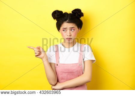 Upset Frowning Teenage Girl Sulking, Pointing Fingers Left With Jealous Unfair Face, Standing Disapp