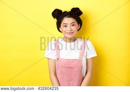 Cute Asian Woman With Makeup And Summer Clothes, Smiling Silly And Happy At Camera, Yellow Backgroun