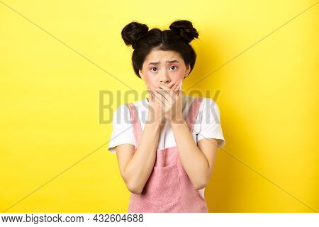 Worried Asian Teen Girl Covering Mouth With Hands, Looking Concerned And Anxious, Standing Scared On