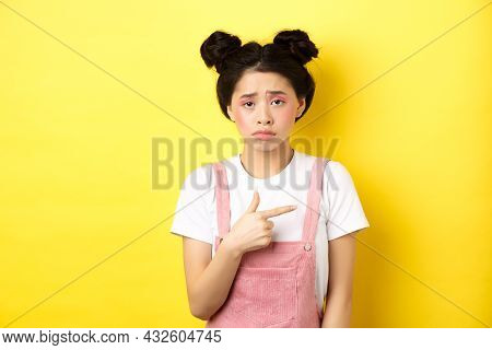 Sad And Disappointed Asian Girl Frowning, Feel Unfair, Pointing Finger Right At Bad Thing, Complaini