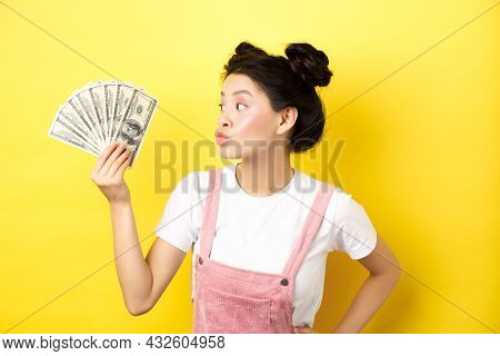 Shopping. Silly Korean Girl With Glam Makeup, Pucker Lips And Looking At Dollar Bills, Wasting Money