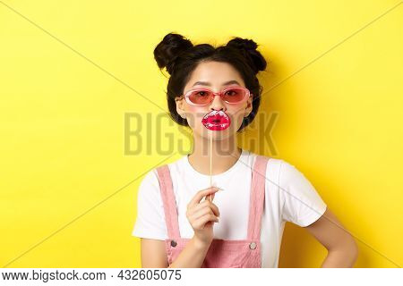 Summer And Fashion Concept. Stylish Asian Glam Girl In Sunglasses, Holding Party Lips Mask, Standing
