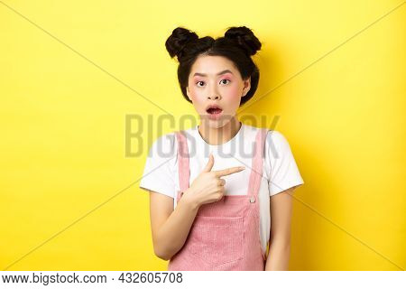 Shocked Asian Woman With Glamour Makeup, Open Mouth And Pointing Right At Logo, Showing Advertisemen