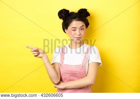 Glamour Asian Girl With Bright Makeup, Pointing Finger Left And Winking At Camera, Hint On Good Prom