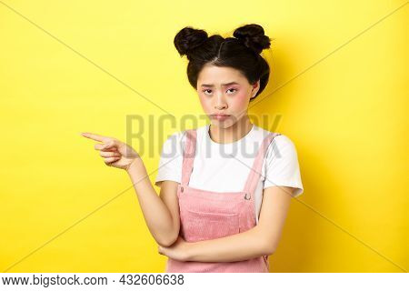 Sad And Gloomy Asian Girl With Glamour Makeup, Frowning Unfair And Pointing Left At Logo, Looking Di
