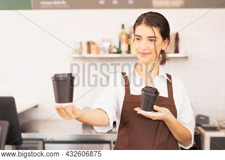 Beautiful Caucasian Barista Woman Show Takeaway Coffee Cup In One Hand And Hold Coffee Cup In Anothe