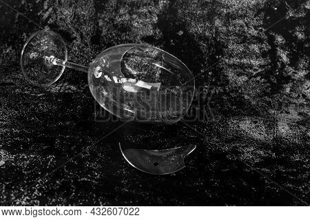 Broken And Smashed Wineglass On A Black Background