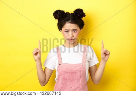 Sad And Gloomy Asian Woman Frowning, Pointing Fingers Up And Complaining On Unfair Thing, Standing U