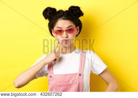 Stylish Glam Girl With Sunglasses, Pouting And Poking Cheek, Standing Silly On Yellow Background