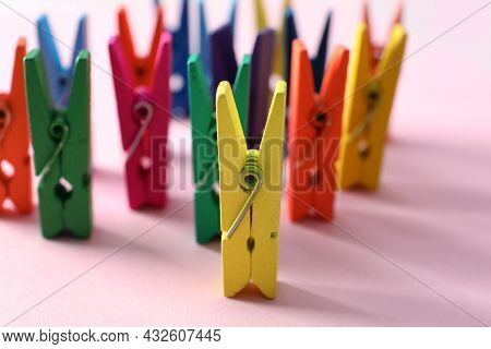 Many Different Colorful Clothes Pins On Pink Background. Diversity Concept