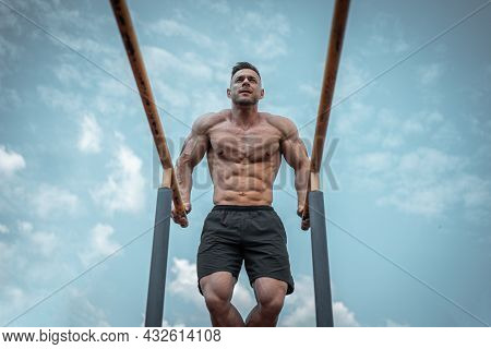 Attractive Muscular Athlete Man Or Bodybuilder Pull Up And Exercising Outdoor