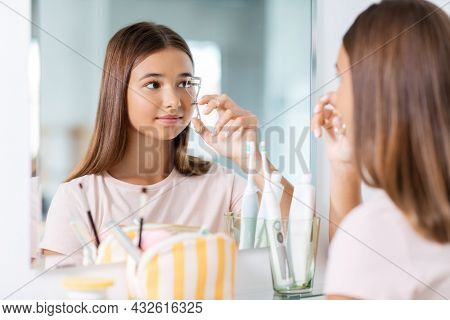 beauty, make up and cosmetics concept - teenage girl curling her lashes and looking to mirror at home bathroom