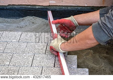 The Hands Of A Bricklayer In Construction Gloves Hold A Level For Leveling The Surface Of Granite Pa