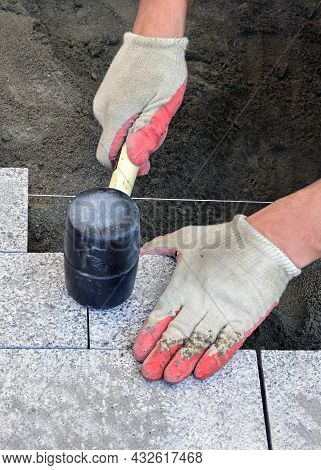 The hands of a bricklayer in construction gloves hold a mallet-hammer for leveling the surface of granite paving stones when laying a pedestrian sidewalk on a street in the city. Road construction works. Improvement of the city.