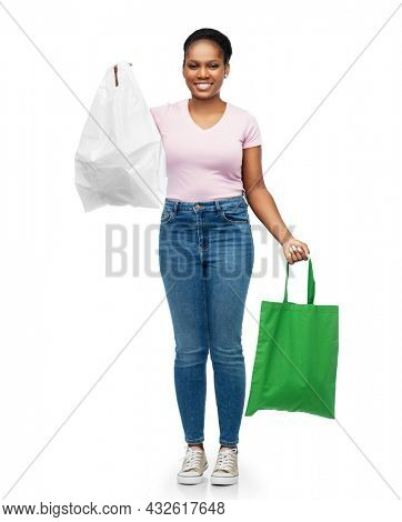 sustainability and people concept - happy smiling young african american woman comparing green reusable canvas bag for food shopping with plastic bag over white background