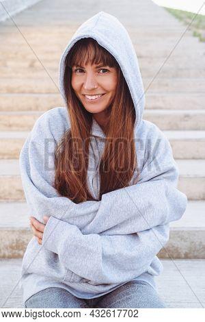 Beautiful Woman In Grey Sweatshirt Seats On A Stairs.