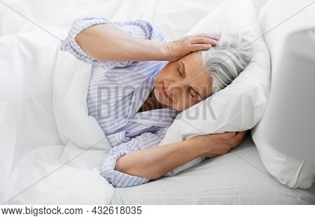 bedtime, rest and old people concept - annoyed senior woman in pajamas suffering from headache lying in bed at home bedroom