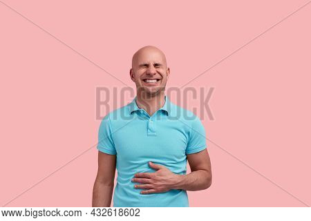 Funny Bald Homosexual Man With Bristle Laughs Out Loud, Touches Stomach With Hand, Closes Eyes, Grim