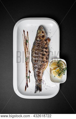 Close Up Of Whole Grilled Stuffed Fish Sea Bass With Lemon On Black Background
