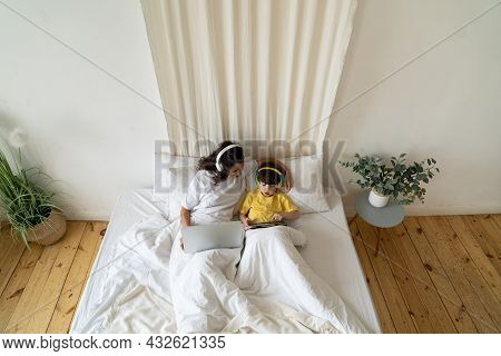 Mother Work From Home Remotely While Being On Coronavirus Sick Leave Lying In Bed With Cute Preschoo