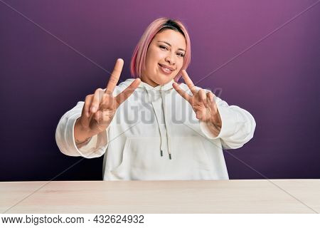 Hispanic woman with pink hair wearing casual sweatshirt sitting on the table smiling looking to the camera showing fingers doing victory sign. number two.