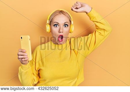 Young blonde woman dancing wearing headphones afraid and shocked with surprise and amazed expression, fear and excited face.