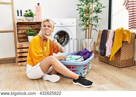 Young caucasian woman putting dirty laundry into washing machine cutting throat with hand as knife, threaten aggression with furious violence