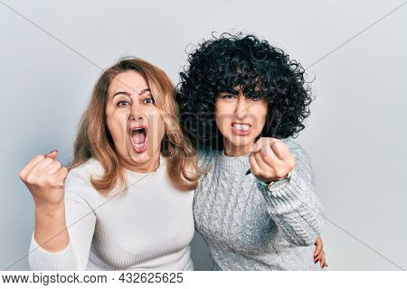 Middle east mother and daughter wearing casual clothes angry and mad raising fist frustrated and furious while shouting with anger. rage and aggressive concept.