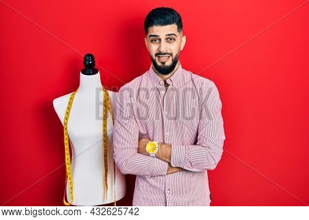 Handsome tailor man with beard with arms crossed gesture clueless and confused expression. doubt concept.