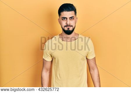Handsome man with beard wearing casual yellow t shirt puffing cheeks with funny face. mouth inflated with air, crazy expression.