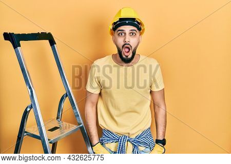 Handsome man with beard by construction stairs wearing hardhat afraid and shocked with surprise and amazed expression, fear and excited face.